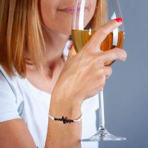 Girl holding a glass of wine wearing Bracelet_Carbon_fiber_Pulse_white_string2-zakcode